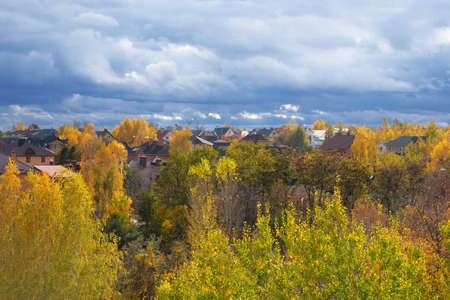 Autumn on outskirts of residence complex. Clouds in bright blue sky. Landscape of September, October, November. Colorful trees. Zdjęcie Seryjne