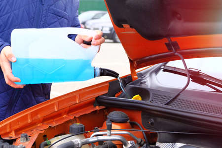 Driver with blue washer fluid in his hands, close up. Car maintenance concept. Filling windshield washer fluid on orange car.