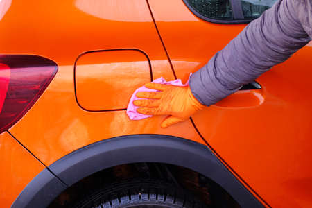 Man after cleaning wipes his orange car with a pink rag  at car wash. Male hand and car body closeup. 免版税图像