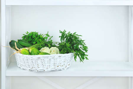 Green autumn vegetables in basket on shelf in wooden rack near a white wall. Copy space for putting text.