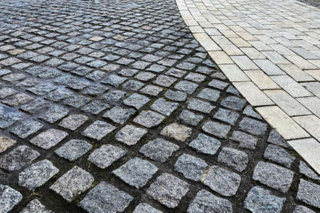 Pavement is lined with old stone. Gray retro stone texture. Pedestrian zone in the park in daylight. Urban walkway. Banco de Imagens