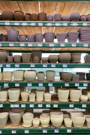 Flower pots are sold at the store. Rows of different beige and purple pots for indoor plants on shelves in a supermarket. Vertical view.