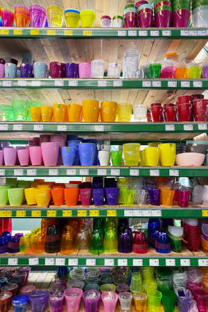 Variety of flower pots are sold at the store. Rows of different colorful pots for indoor plants on shelves in a supermarket. Vertical view.