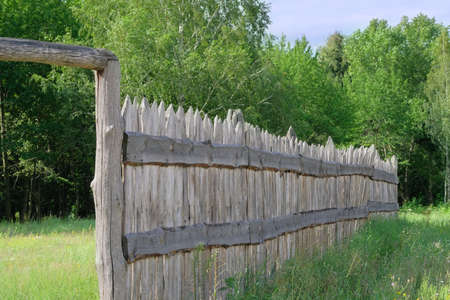 Wooden rustic fence in village near the forest. Authentic traditional culture in architecture and life. Sunlight, old wood.