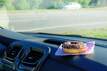 Donut for lunch. Chocolate nut snack on console in auto. Lunch break while traveling by car. Takeaway, social media. Banco de Imagens