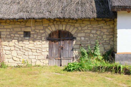 Old rural house with thatched roof. Village is preserving rustic traditions and culture. Banco de Imagens