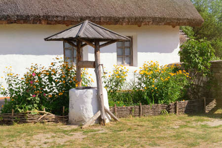 Old well near a rural hut with whitewashed walls. Village is preserving rustic traditions and culture. Banco de Imagens