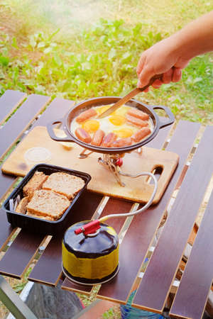 Camping food making. Fried eggs and sausages on pan on tourist gas burner. Camper preparing food in the forest. Banco de Imagens