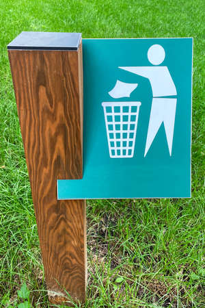 Sign of throw the trash in the trash can on background of green grass in park. Symbol on metallic plate.
