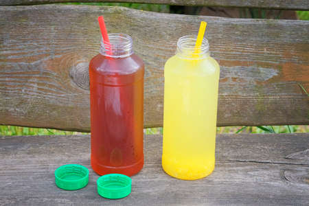 Orange and fruit lemonade in bottles with a straw on wooden terrace. Summer minimalism. Banco de Imagens