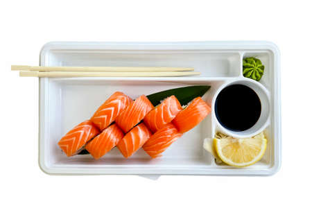 Sushi set in box isolated on white background. Japanese sushi, philadelphia rolls, soy sauce, ginger, chopsticks. Top view. Banco de Imagens