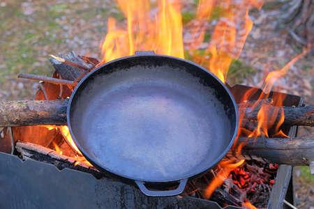 Cast iron skillet over an red fire heats up for further cooking. Firing a cast iron skillet over an open fire. Фото со стока