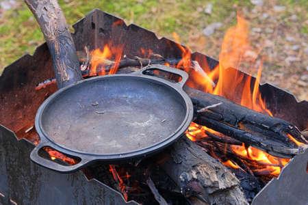 Firing a cast iron skillet over an open fire. Cast iron skillet over an red fire heats up for further cooking Фото со стока