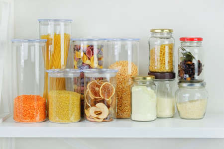 Variety of grain products and pasta in glass storage containers on white wooden table. Healthy cooking, clean eating, zero waste concept. Balanced dieting food.