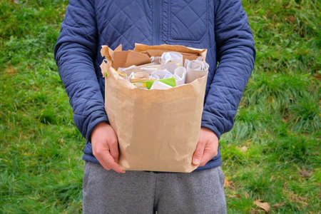 Paper and cardboard prepared for recycling. Bundles of cardboard to be recycled. Man holds a package of paper and cardboard in his hand for recycling.