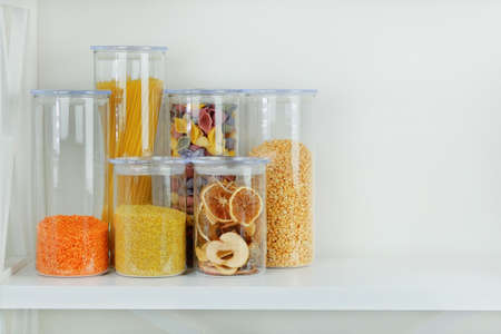 Assortment of grain products and pasta in glass storage containers on white wooden table. Healthy cooking, clean eating, zero waste concept. Balanced dieting food.