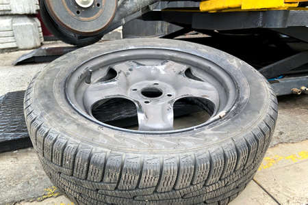 Wheel balancing or repair and change car tire. Automobile maintenance concept. Damaged tire in car.