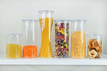 Assortment of uncooked grains, cereals and pasta in glass jars on white wooden table. Healthy cooking, clean eating, zero waste concept. Balanced dieting food.