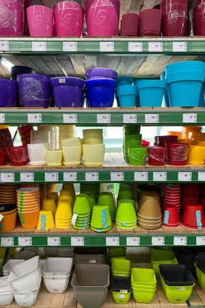 Variety of colorful flower pots are sold at the store. Rows of different pots for indoor plants on shelves in a mall. Vertical view.