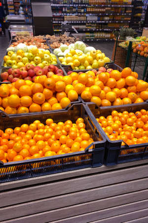 Tangerines, oranges, apples and other fruits are sold in the store. Vertical image.