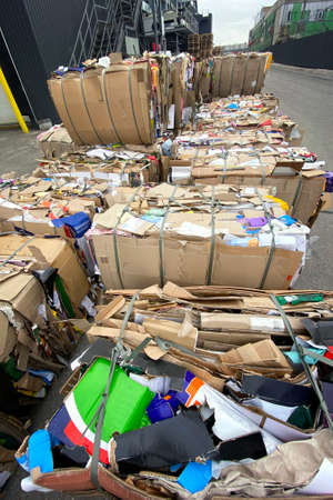 Cardboard and waste paper is collected and packaged for recycling. Cardboard is bundled into bales. Urban Recycling and storage. Фото со стока