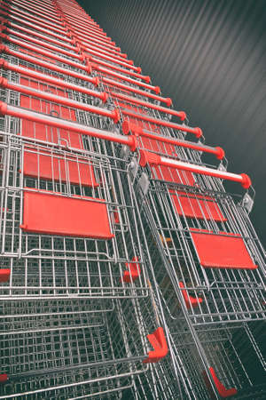 Shopping metallic cart lined up in rows in the shop parking. Supermarket aisle with empty red shopping cart.