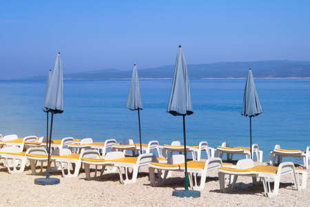 Blue umbrellas and chaises for relax on sea coast. Summer vacations and travel concept. Paid service on beaches.