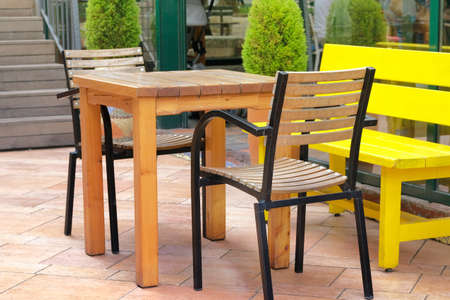 Empty patio in summer in recreation. Table and armchairs on outdoor terrace of summer cafe.