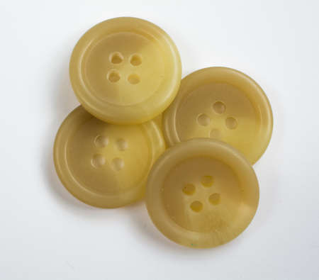 cream colored: Four Cream Colored Plastic Buttons Stacked and Isolated on White