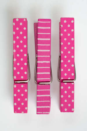 clothes pins: Three Pink Clothes Pins with Fun Patterns Top View Stock Photo