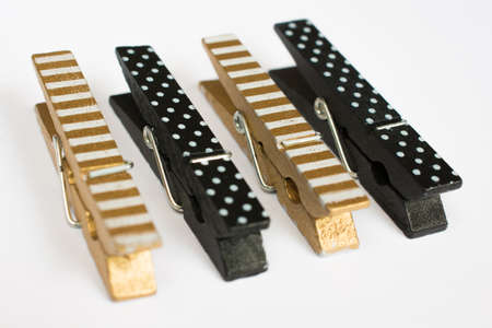 clothes pins: Four Gold and Black Clothes Pins with Fun Patterns Perspective View Stock Photo