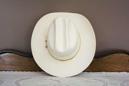 rawhide: A White Cowboy Hat on an Antique Cabinet Front View