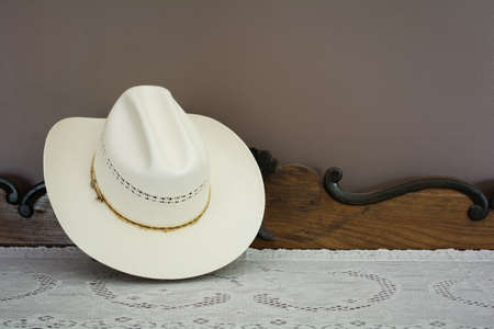 black hat: A White Cowboy Hat on an Antique Cabinet Stock Photo