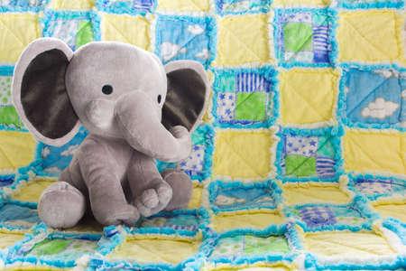 かわいい象の赤ちゃん、カラフルなキルトに動物のぬいぐるみ