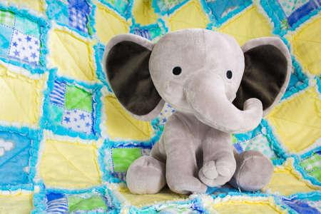 カラフルなキルトにかわいい赤ちゃん象ぬいぐるみをクローズ アップ