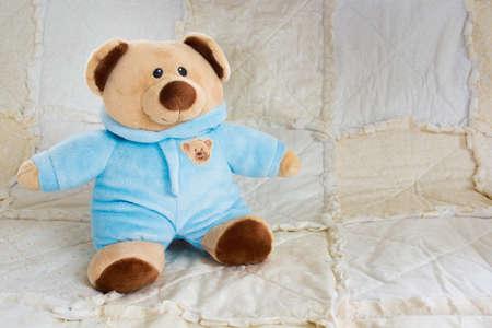 sitt: Cute Bear Stuffed Animal on a White Quilt Stock Photo