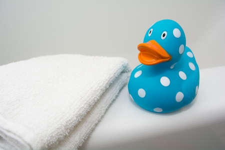 Cute Rubber Duck beside a White Towel in a Bathroom Stock Photo