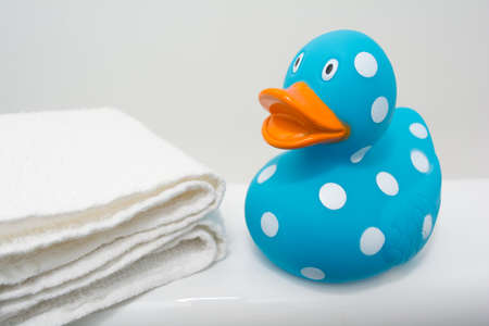 squeaky clean: Cute Rubber Duck beside White Towel in Bathroom Close Up