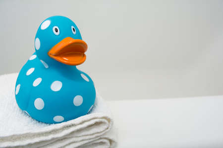 Cute Rubber Duck on a White Towel in a Bathroom Close Up