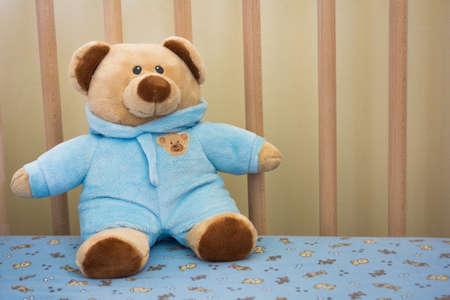 stuffed animal: Cute Teddy Bear Stuffed Animal in a Baby Crib