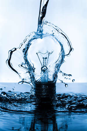 Lightbulb splashed with water on dark surface with blue hue