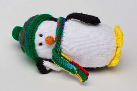 Penguin stuffed toy on white background lying down on white