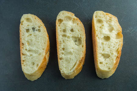 Three sliced baguette pieces on black surface top view Stock Photo