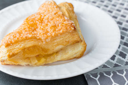 Apple turnover pastry on plate with gray napkin cloth