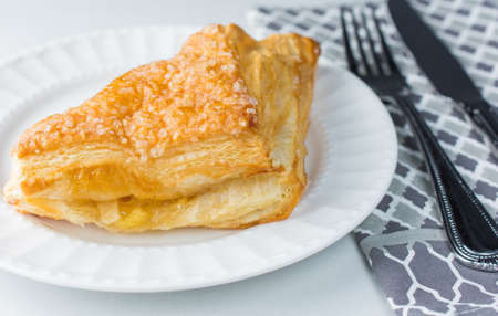 Apple turnover pastry on plate with utensils and cloth
