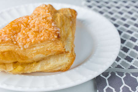 Apple turnover pastry on plate with white background and cloth