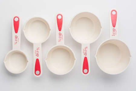 Set of Measuring Cups Staggered on White Background Top View