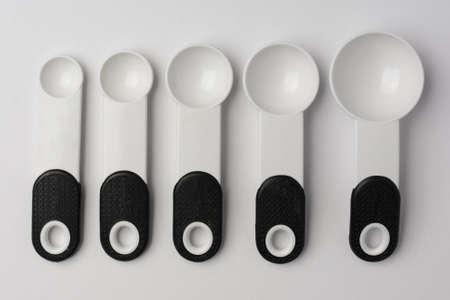Set of Measuring Spoons Lined on White Background Top View