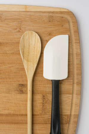 Silicone Spatula and Wooden Spoon on Wooden Cutting Board Stock Photo