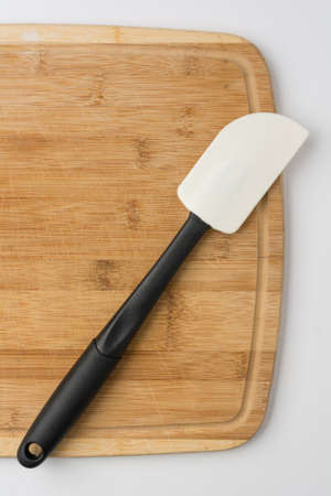 Silicone Spatula Angled on Wooden Cutting Board on White Background Stock Photo